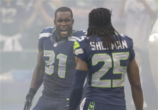Seattle Seahawks cornerback Richard Sherman, right, greets teammate Kam Chancellor, left before an NFL preseason football game against the Oakland Raiders, Thursday, Aug. 29, 2013, in Seattle. (AP Photo/Elaine Thompson)